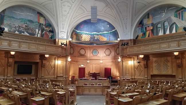 A chamber of Sweden's parliament, adorned with murals and intricate woodwork